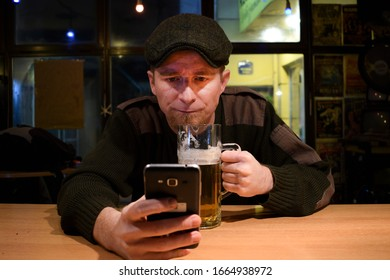Red haired almost Irish guy seating in the bar and drinks some beer and looks at his mobile phone