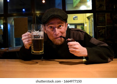 Red haired almost Irish guy seating in the bar and drinks some beer and smokes wooden pipe with funny face