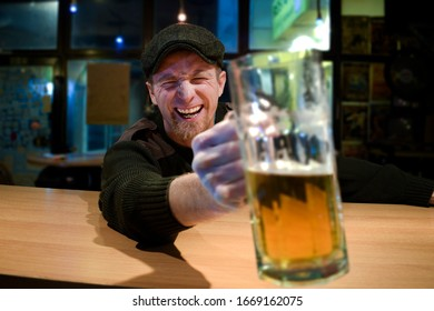 Red haired almost Irish guy seating in the bar and drinks some beer and looks at you and cheers with funny face