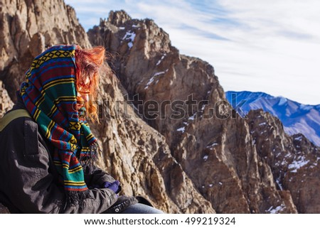 Red haired beautiful girl sitting on the rocks on the top of the Atlas mountains, Morocco.