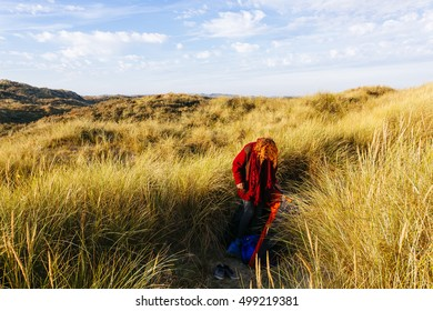Red haired beautiful girl trying to set a tent on the sand dunes in Belgium.