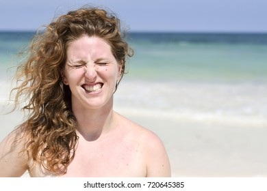 Red haired beautiful woman smiling on the beach on a sunny summer day