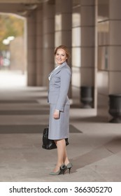 Red haired business women in grey suit and black handbag on smooth background