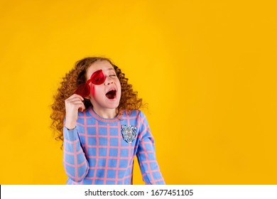 red haired , emotional girl with red glasses on a yellow background