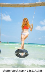 Red haired girl in bikini swinging on the beautiful white sand beach with  crystal water in Phu quoc island Vietnam ,travel concept