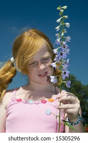 red haired girl with a blue larkspur flower