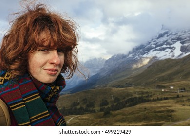 Red haired girl in the mountains in Switzerland
