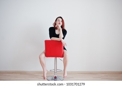 Red haired girl on black dress tunic sitting on red chair against white wall at empty room.