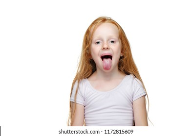Red haired girl put out her tongue against white background