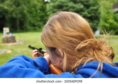 red haired girl shooting a rifle