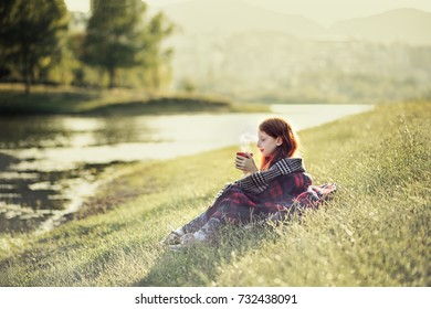 Red haired girl sitting at lake shore, drinking hot tea