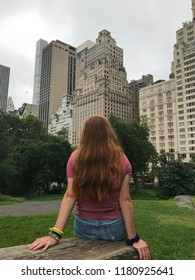 Red haired girl sitting while looking at Manhattan skyline in Central Park, New York City