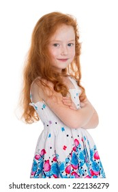 Red haired girl of six years in a summer dress isolated on white background.