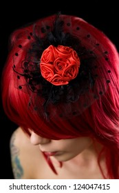 Red haired gothic girl with black feather hair fascinator and red roses