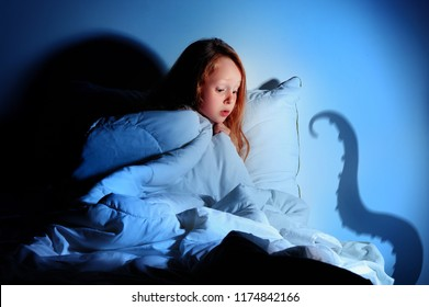 Red haired little girl having fears of night monsters