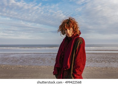 Red haired, pretty, thin, european girl standing in the sunrise on the beach in de Panne in Belgium.