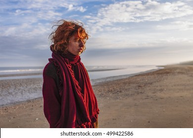 Red haired, pretty, thin, european girl standing in the sunrise on the beach. De Panne, Belgium