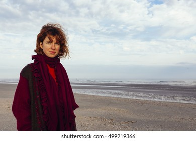 Red haired, pretty, thin, fit girl standing on the beach in Belgium. Wind is blowing on her hair.