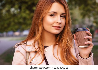 "Red haired sexy plus size woman walking on a park. Cold weather, she wears leather jacket. She drinks coffee from ""to go"" cup"