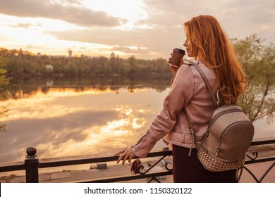 "Red haired sexy plus size woman walking on a park. Cold weather, she wears leather jacket. She drinks coffee from ""to go"" cup. Stunning sunset on a background. Copy space"