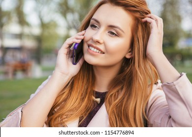 Red haired sexy plus size woman walking on a park. Cold weather, she wears leather jacket. She works on a phone, making calls
