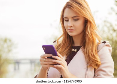 Red haired sexy plus size woman walking on a park. Cold weather, she wears leather jacket. She works on a phone, typing messages