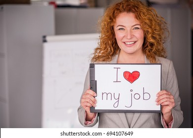Red haired smiling businesswoman holding small poster. Businesswoman happy with her work.