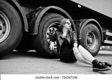 Red haired stylish girl wear in black, sitting against large truck wheels.