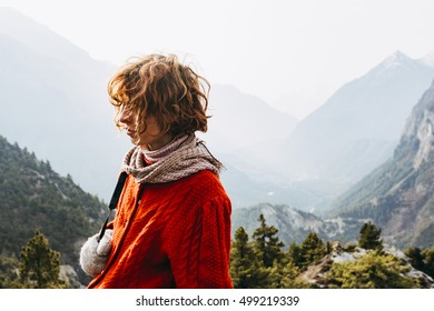 Red haired, thin, pretty girl with the Himalaya mountains in the background, Nepal.