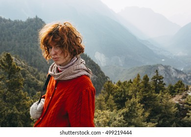 Red haired, thin, pretty girl with the Himalaya mountains in the background in Nepal.