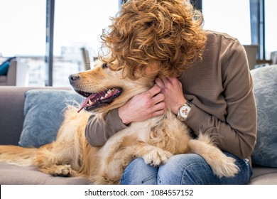 Red haired woman kissing her dog