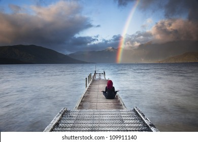 Red haired woman meditating in yoga position on pier overlooking mountains,lake and rainbow