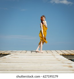 red haired woman at ocean pier in summer