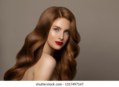 Red haired woman portrait. Young female model with long curly hair on gray background