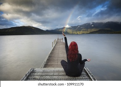 Red haired woman sitting in yoga position on the pier is catching rainbow over the lake