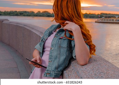 Red haired woman with smartphone in her hands looking back at boat on water in front of sunset. Ginger haired