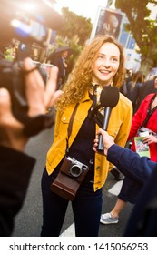 Red haired young millennial teenager with hipster style being interviewed by television in the street, she-s comfortable and happy