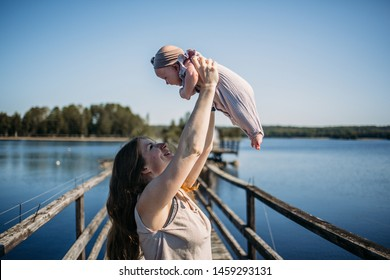 Red haired young woman with her baby daughter are walking on a wooden rustic bridge in republic of Karelia, Russia. Image with selective focus and toning