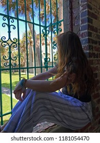 Red haired young woman looking at window at Atalaya Castle, Huntington Beach State Park, Murrells Inlet, South Carolina