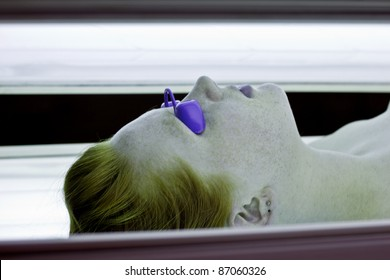 Red haired young woman wearing goggles in lit tanning bed
