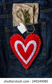 Red hand made heart for Valentine's Day on jeans background. Greeting Card with craft tag for message