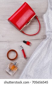 Red handbag, fashion cosmetics, evening dress. Fashion lady accessories set, top view.