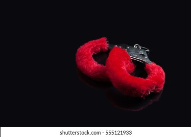 Red handcuffs at black background
