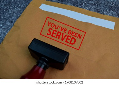 Red Handle Rubber Stamper and You've Been Served text isolated on the table.