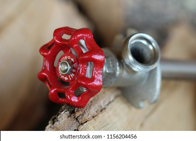 red handle spigot with attached pipe for plumbing closeup
