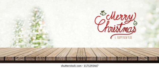 Red handwriting merry christmas and happy new year over wood table top with abstract blur christmas tree and snow fall background with bokeh light.Mock up banner for display or montage of product