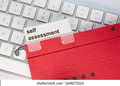 red hanging folder on a keyboard has a tab with the words: self assessment on it