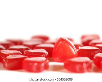 red hard candies closeup on white background, shallow depth of field, selective focus, copy space.