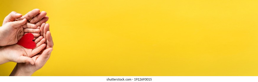 Red hart on palms of mother and son - Caucasian woman and child holding red hart shape above the modern abstract yellow background with copy space - Love care protection motherhood and family concept