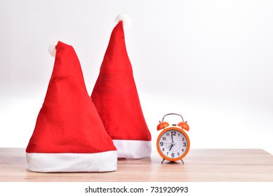 Red hat christmas and alarm clock pace on wood table isolated background.